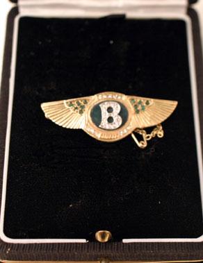Lot 214-Emerald & Diamond Encrusted Gold Bentley Brooch